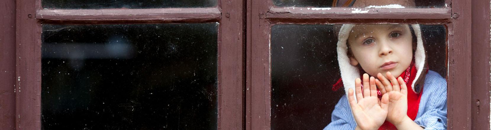 Lockdown e figli, zona rossa e coprifuoco: bambino chiuso in casa che guarda fuori e vuole uscire.