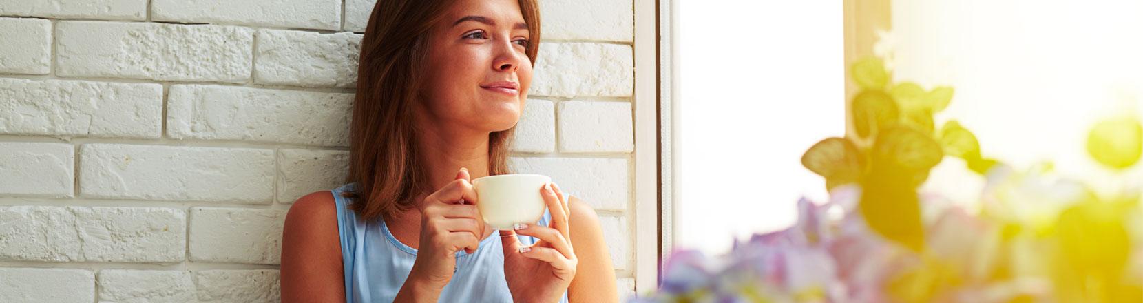 Donna che sorride al mattino mentre fa colazione