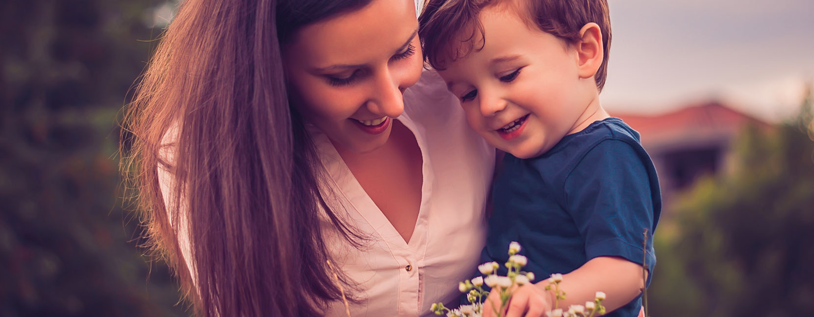 Mamma con il suo bambino raccolgono dei fiori