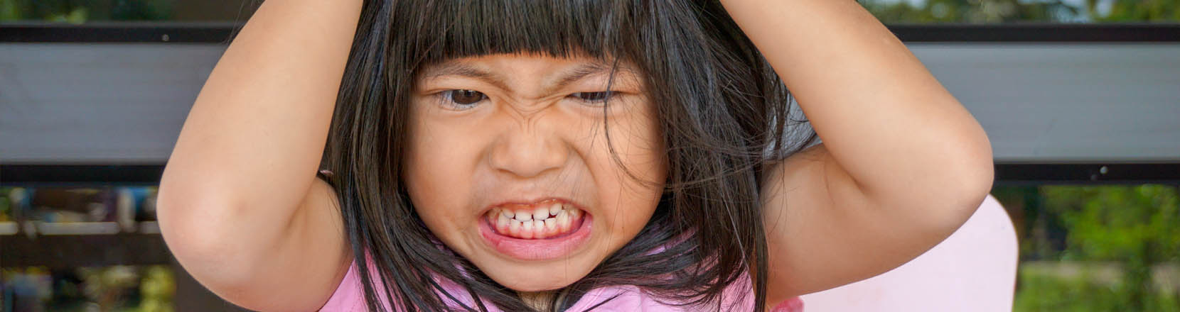 Bambina arrabbiata digrigna i denti e si strappa i capelli