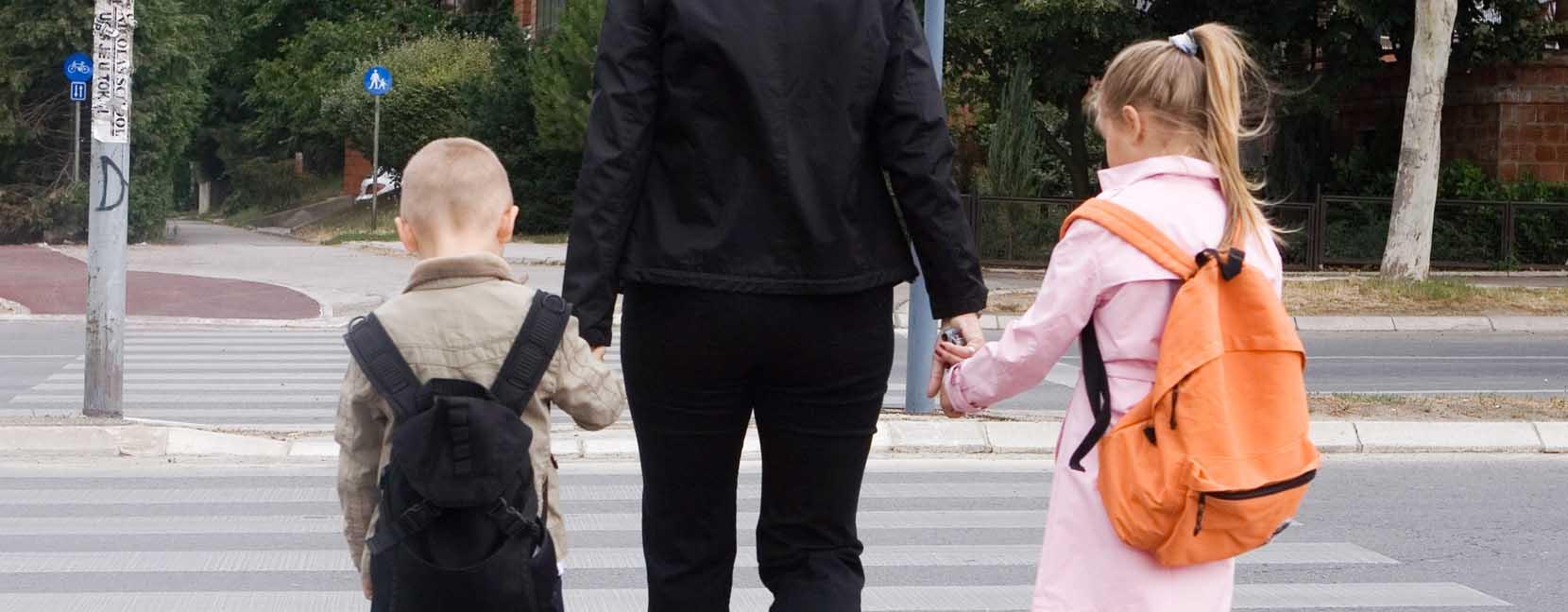 Mamma attraversa la strada tenendo per mano i suoi bambini