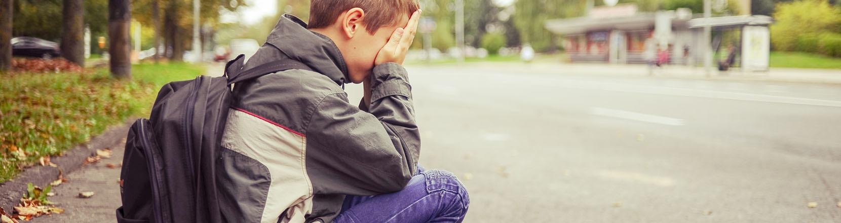 Ragazzino triste piange seduto sul marciapiede, scarsa autostima
