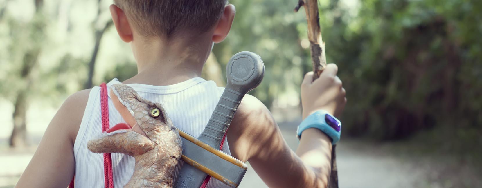 Bambino cammina all'avventura con bastone in mano e zainetto con spada e dinosauro