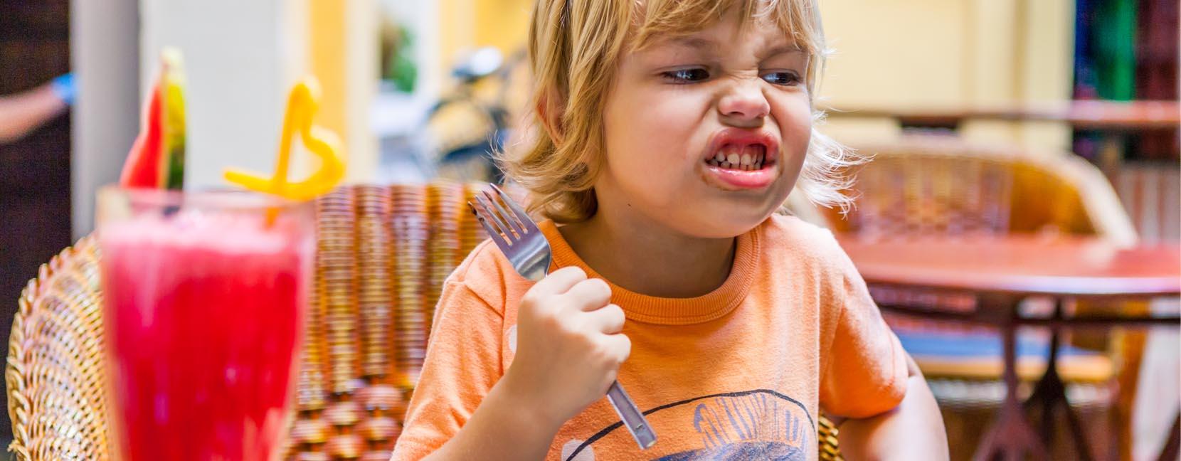 Bambino arrabbiato stringe in mano una forchetta minaccioso