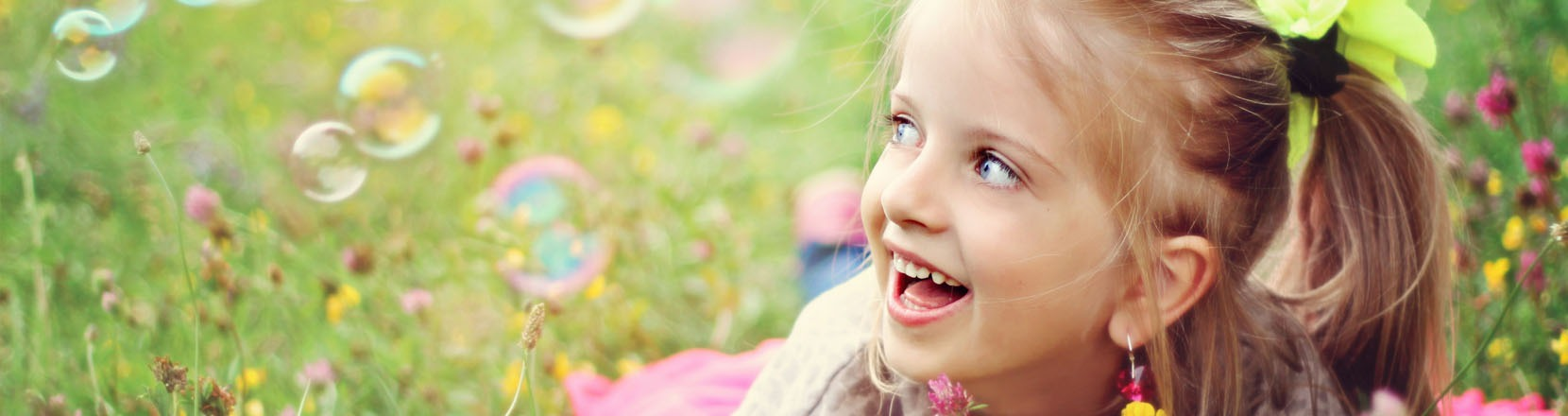 Bambina distesa in un prato che sorride in mezzo alle bolle di sapone