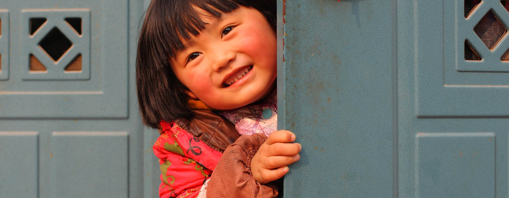 Bambina spunta nascosta dietro una porta