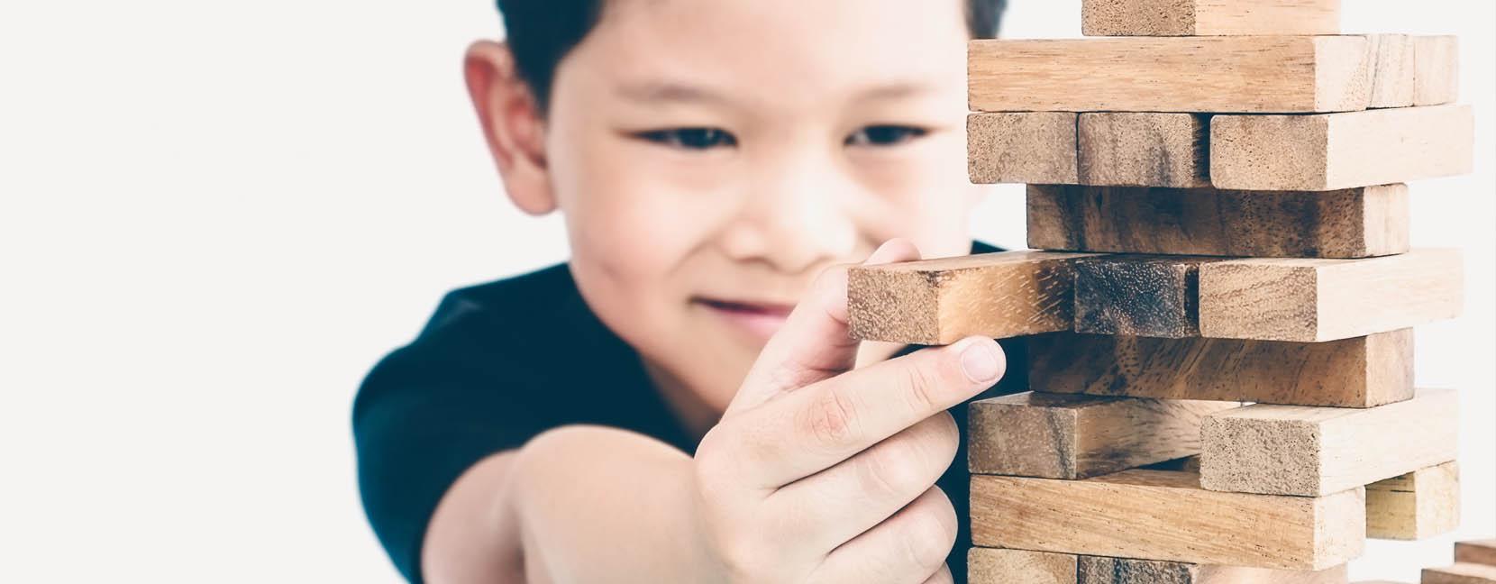 Bambino che sfila un mattoncino di legno da una torre