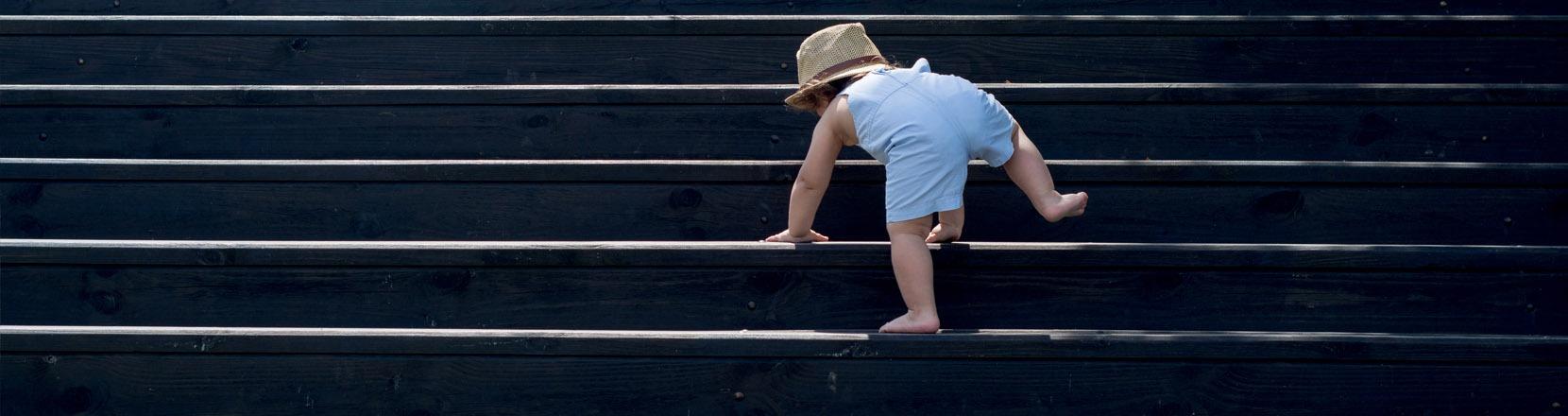 Bambino piccolo sale le scale da solo