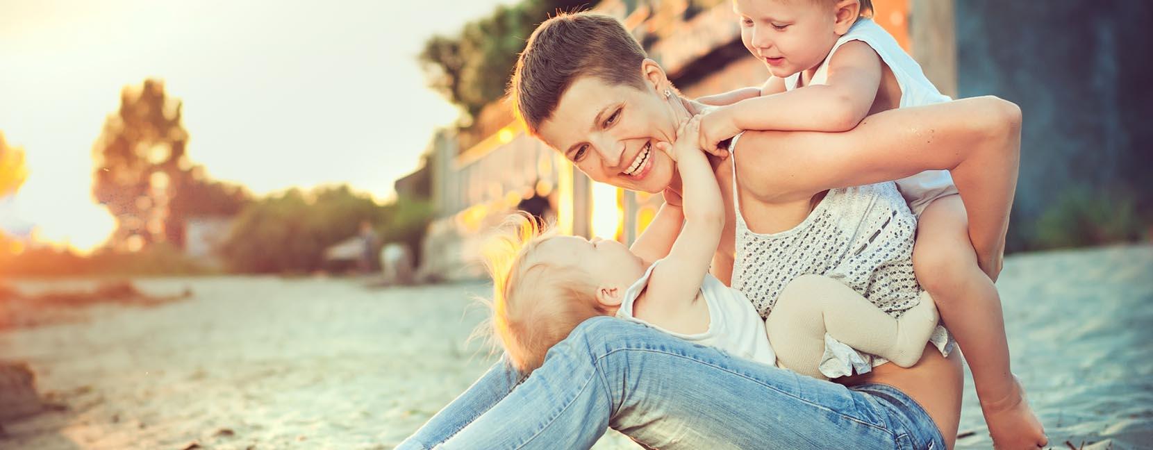 Mamma sorridente seduta con un bambino in braccio e l'altro sulla schiena: giocano