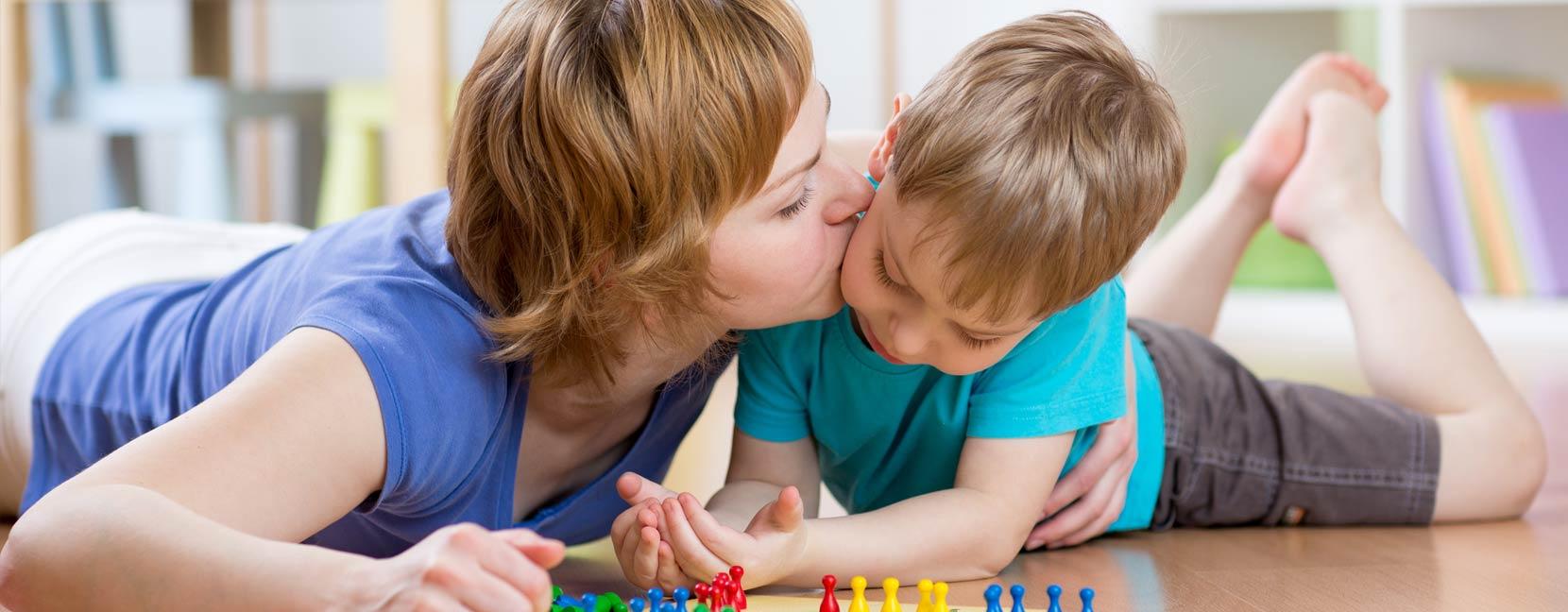 Mamma da un bacio al suo bimbo che ha un espressione rattristata