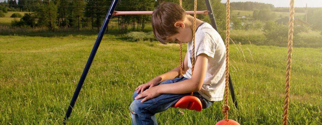 Frasi che distruggono l'autostima: Bambino triste seduto su u'altalena