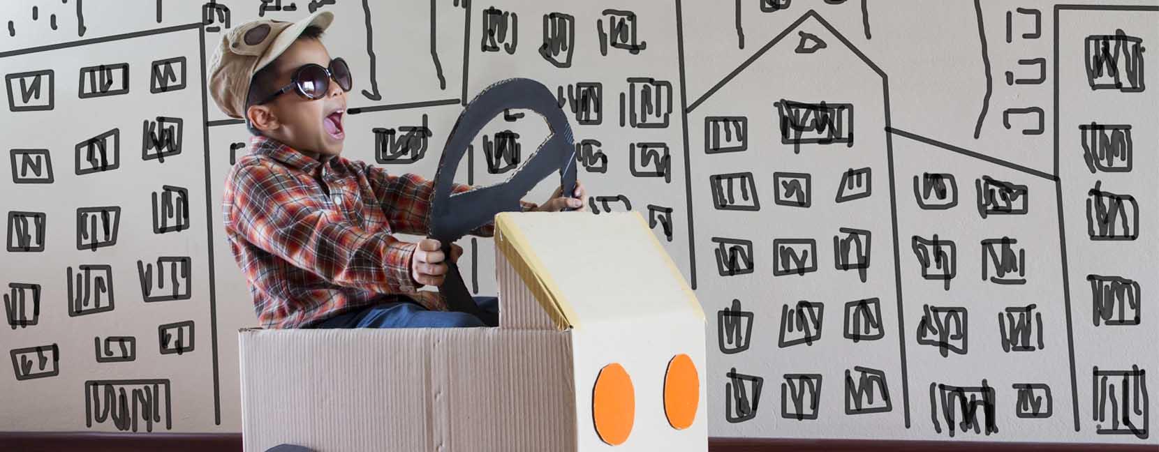 Bambino felicissimo alla guida di una macchina di cartone