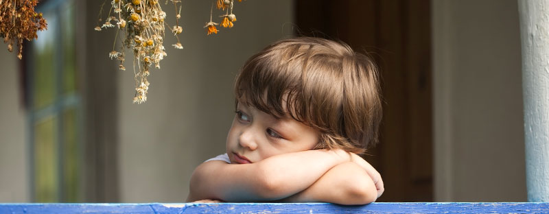 Bambino triste appoggiato ad un muretto