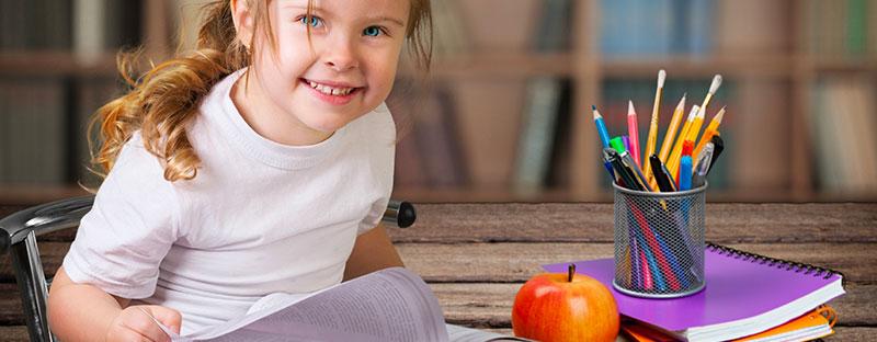 Bambina pronta a scrivere con quaderno e penne