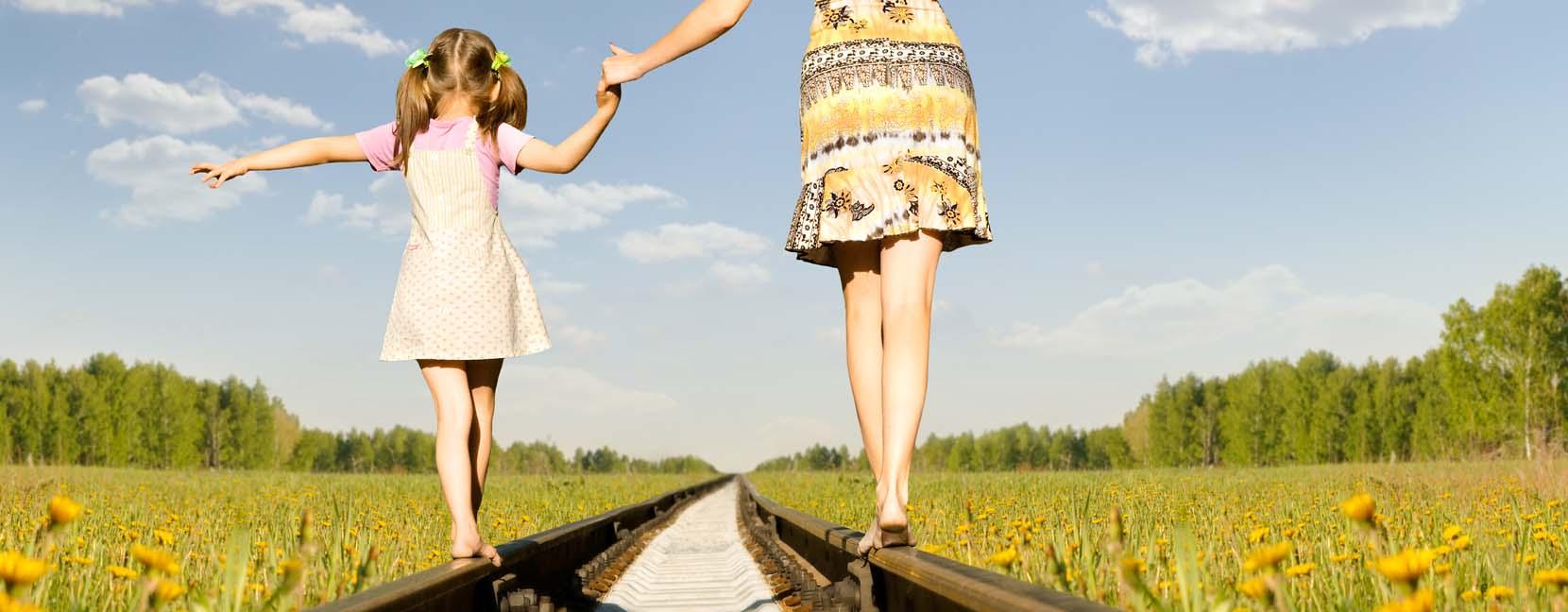 Mamma e figlia camminano in equilibrio sulle rotaie, hanno sicurezza e fiducia in se stesse