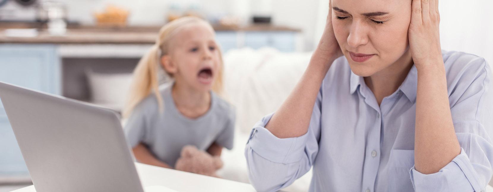Bambina che urla arrabbiata e mamma che reagisce tappandosi le orecchie e chiudendo gli occhi