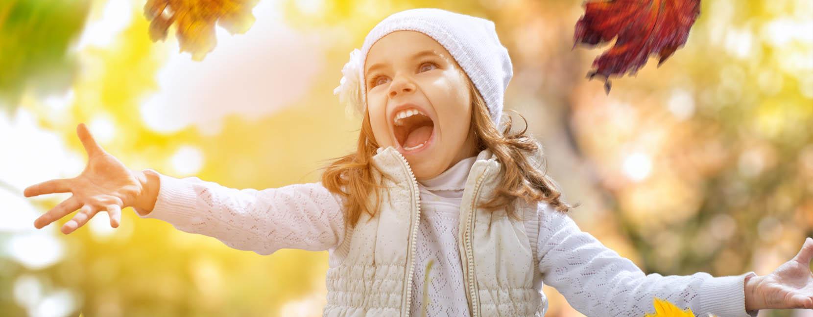 Bambina che lancia urlando delle foglie contenta
