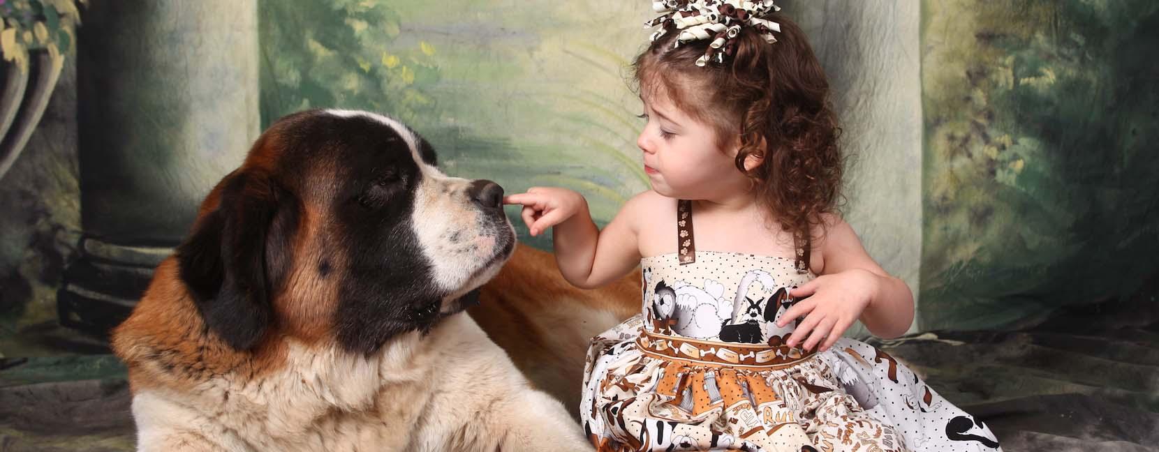 Bambina che tocca il naso di un grosso cane tranquillo