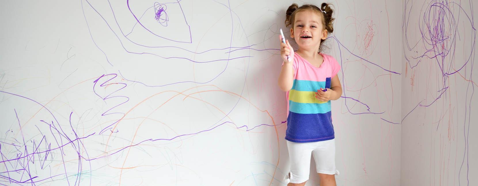 Il desiderio di sperimentare e apprendere: bambina che ha disegnato con il pennarello sul muro