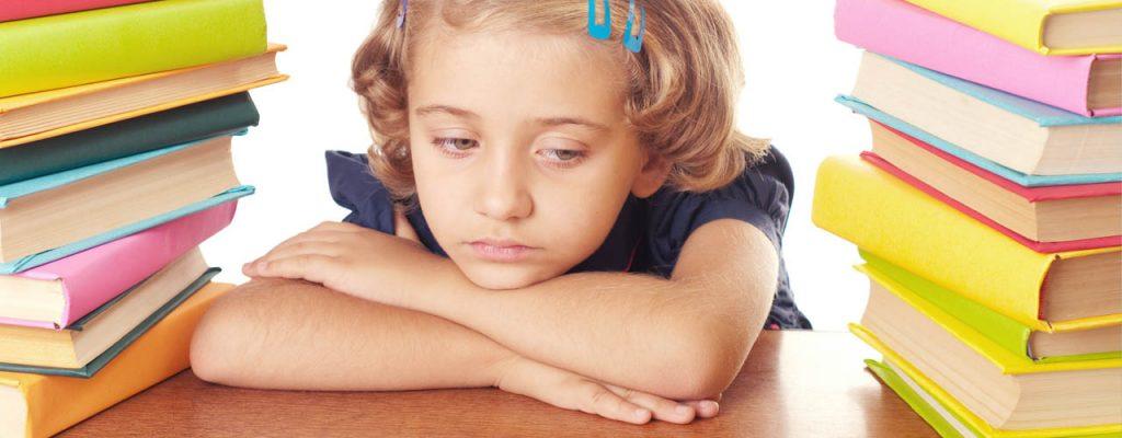 Bambina si appoggia alla scrivania annoiata tra pile di libri, odia i compiti