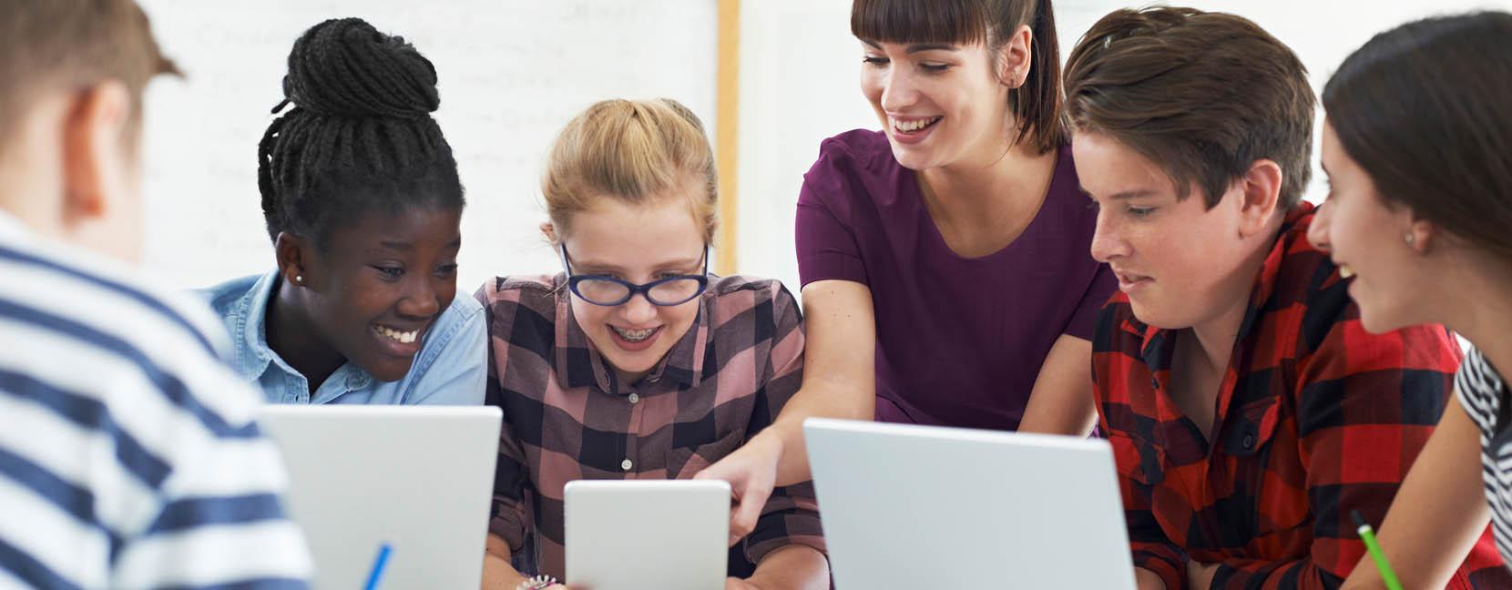 Ragazzi che studiano insieme con computer e pad