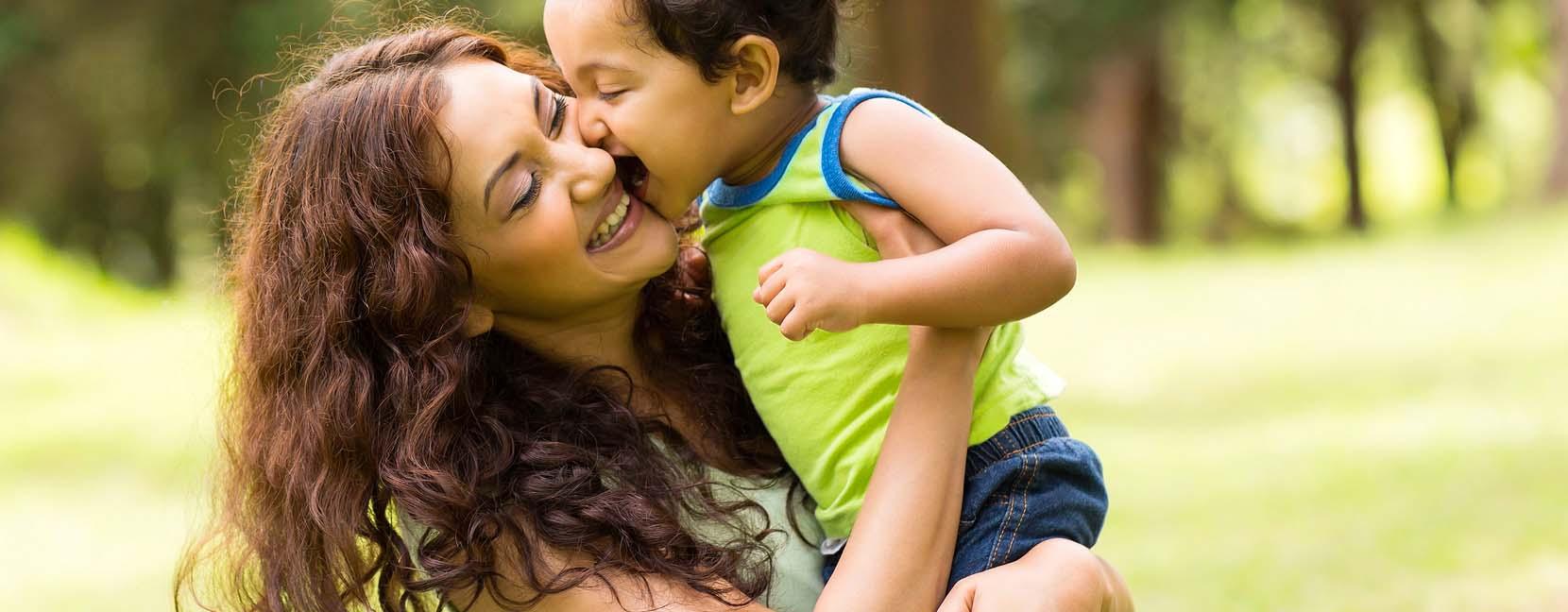 Mamma felice che tiene il suo bimbo sorridente in braccio.
