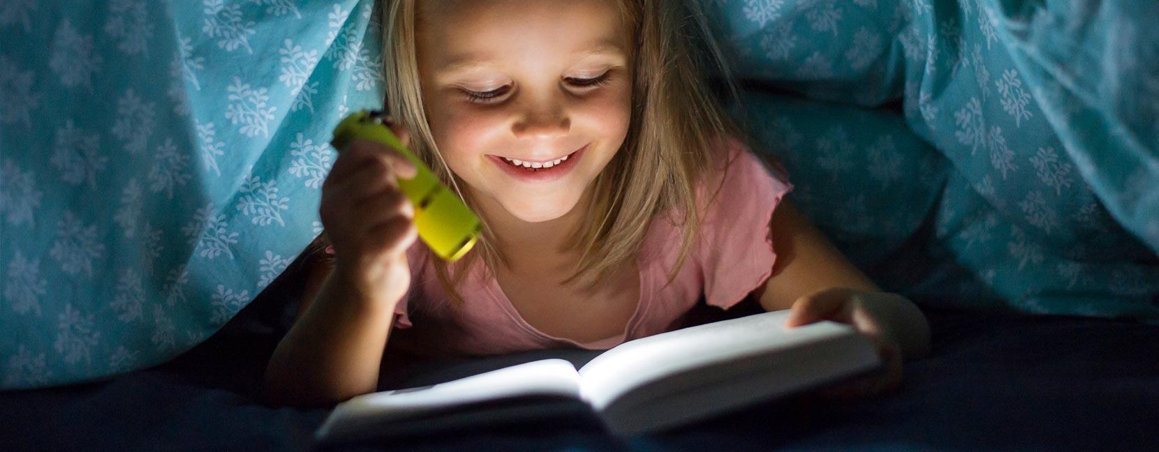 Bambina legge un libro di notte sotto la coperta con una torcia