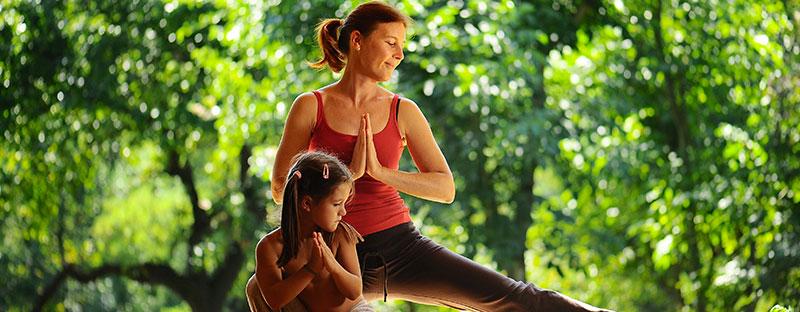 Mamma e figlia calme in una posizione yoga