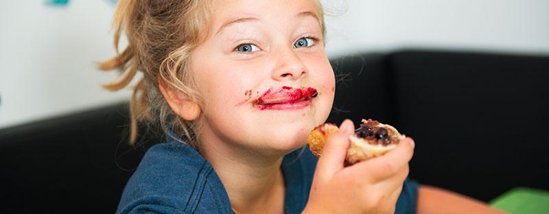 Bambina soddisfatta e felice mangia pane e marmellata