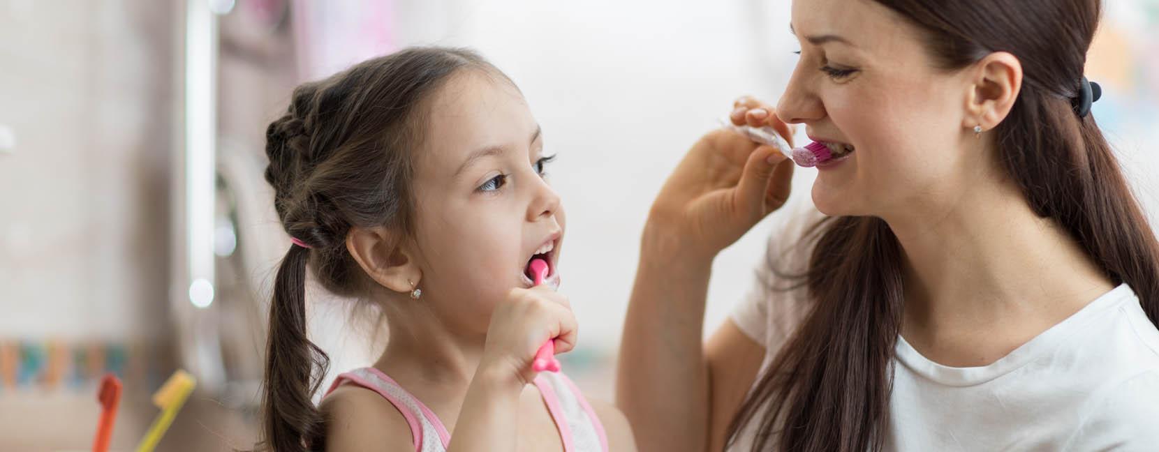 Mamma e figlia si lavano i denti insieme con viso sorridente