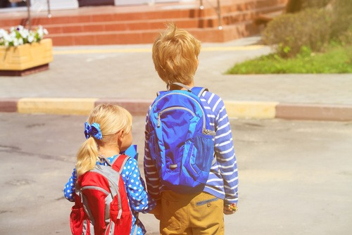 kids go to school- little boy and girl with backpacks on the str