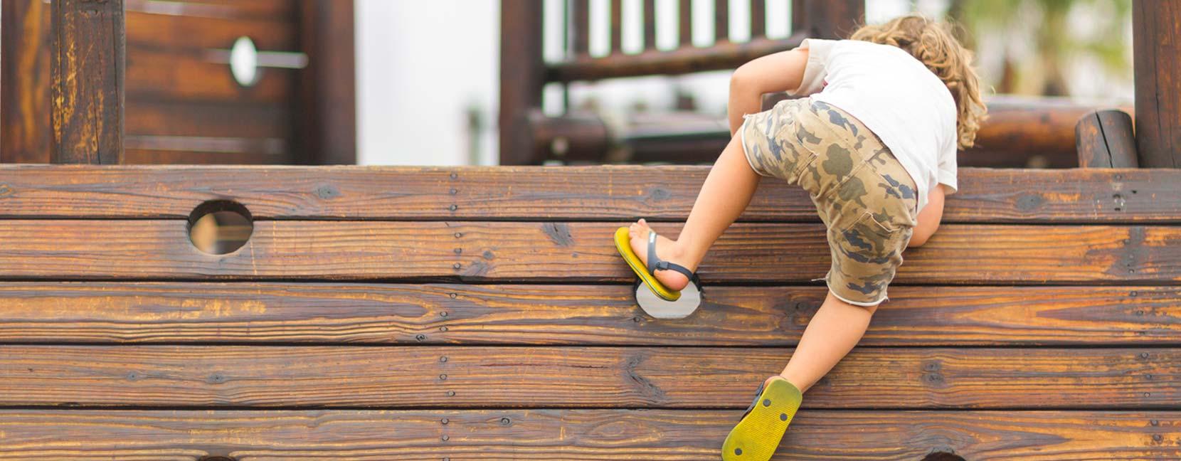 Bambino si arrampica su un muro-ostacolo