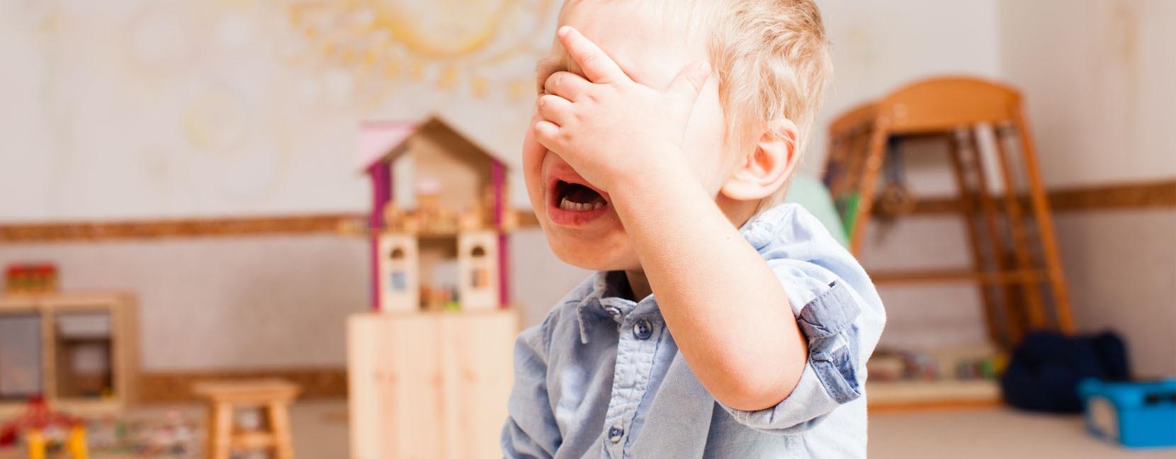 Bambino piccolo che piange tenendo la mano sugli occhi
