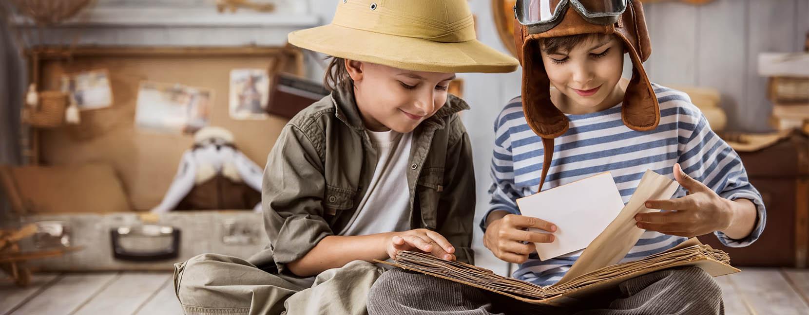 Bambini travestiti da esploratori che guardano un libro antico