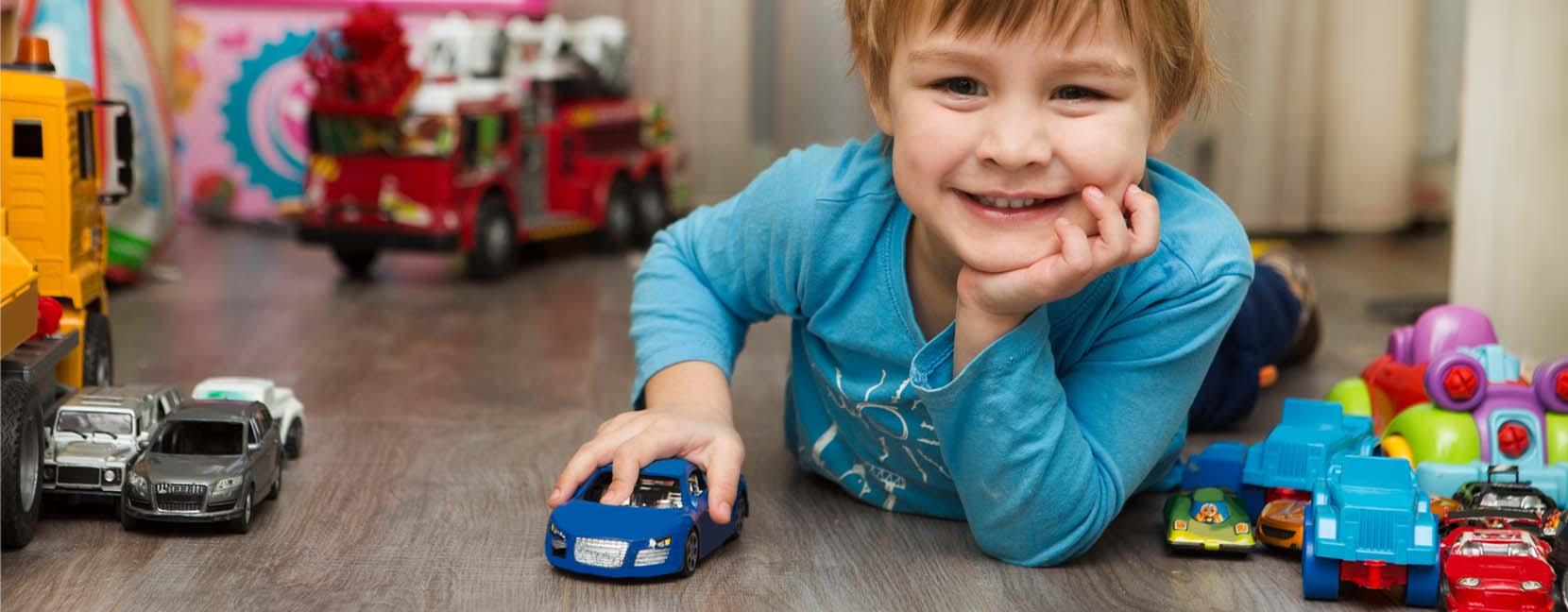 Bambino che gioca con le macchinine, circondato da giochi