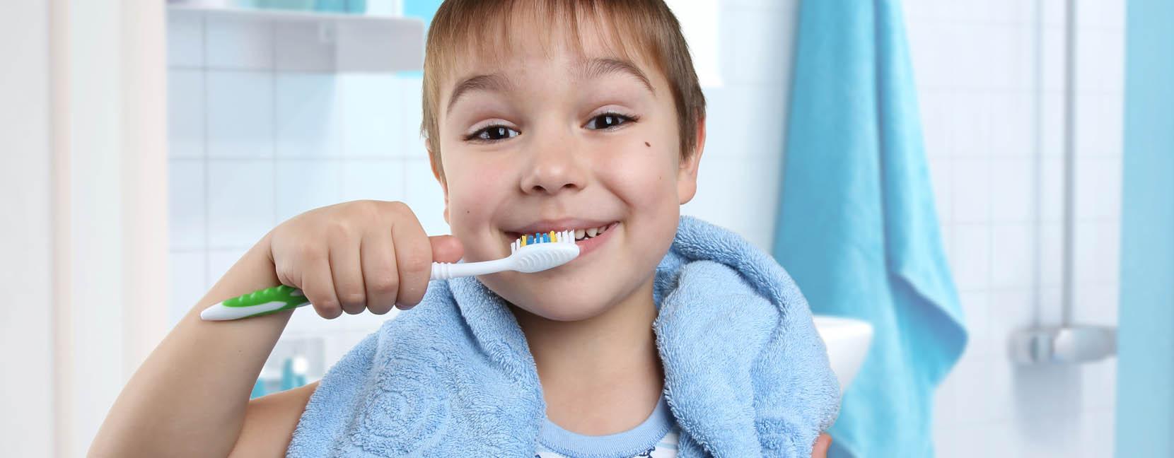 Bambino sorridente che si lava i denti seguendo le regole