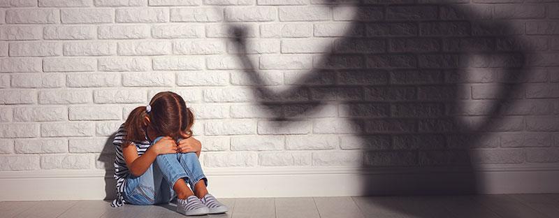 Bambina rannicchiata, si vede l'ombra del genitore che la sgrida duramente