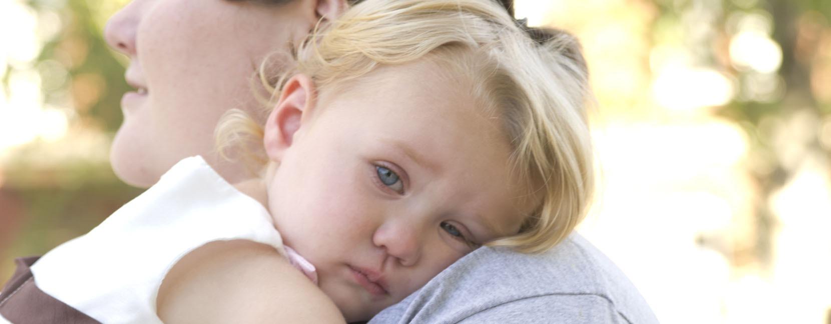 Bambina piccola che si appoggia triste sulla spalla della mamma
