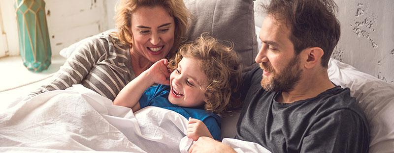 Bimbo felice nel lettone in mezzo a mamma e papà