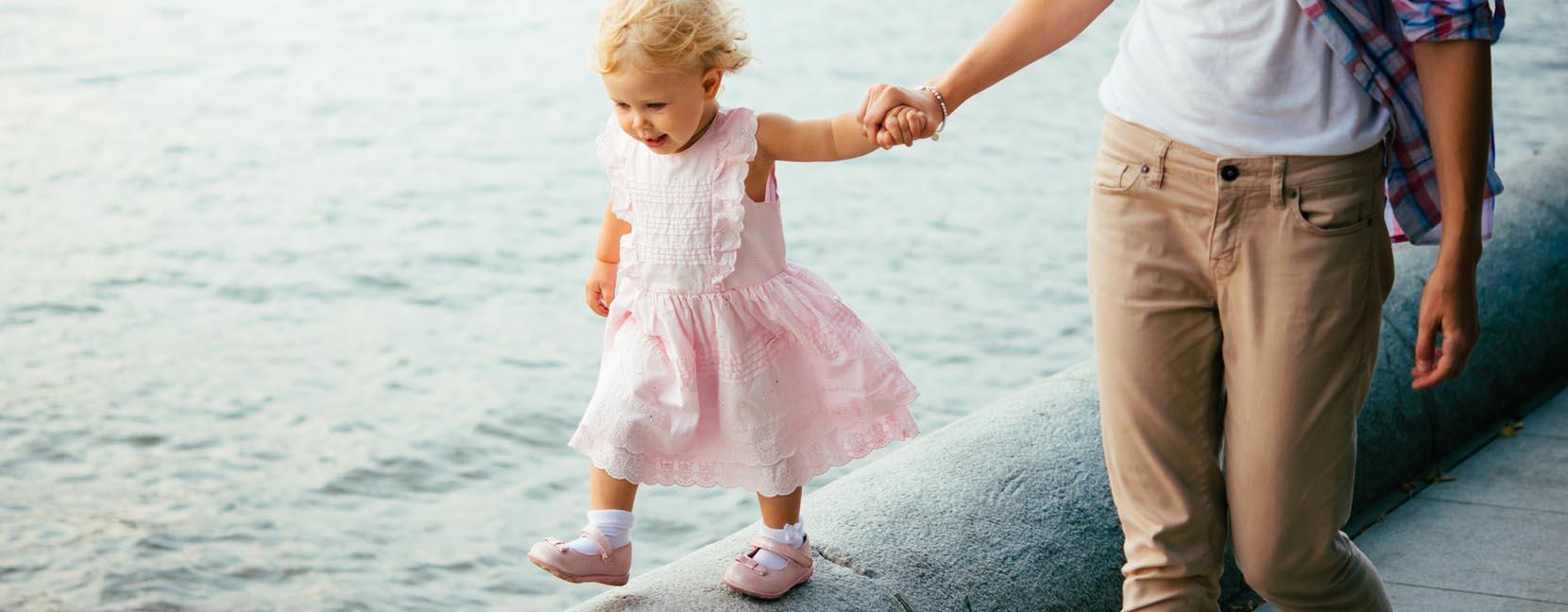 Mamma tiene la mano alla bimba mentre passeggia sul muretto che separa la strada dal mare