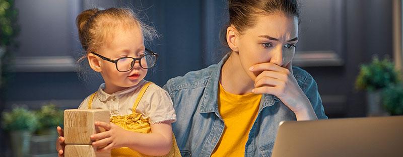 Mamma guarda preoccupata il computer e la figlia piccola indossa i suoi occhiali